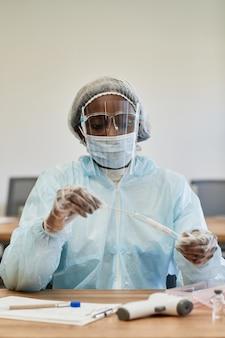 Infirmière médicale sérieuse en costume ppe mettant un écouvillon de test covid dans un tube à essai à envoyer au laboratoire