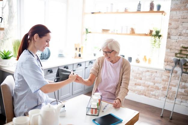 Infirmière mesurant la pression artérielle d'une dame à la retraite