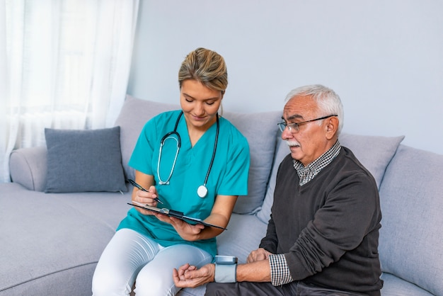 Infirmière mesurant la pression artérielle d'un homme senior à la maison.