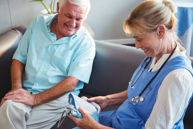 Infirmière mesurant la pression artérielle d'un homme senior