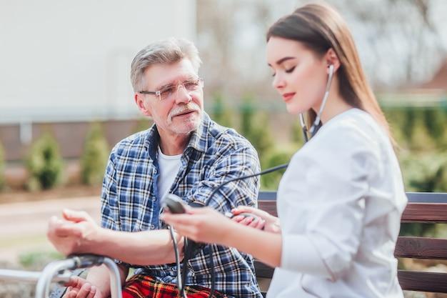 L'infirmière mesure le pouls d'un vieil homme dans le jardin de la clinique