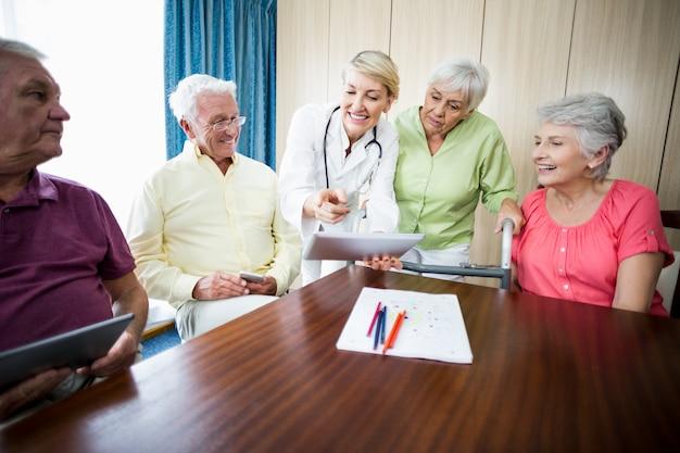 Infirmière montrant quelque chose aux personnes âgées