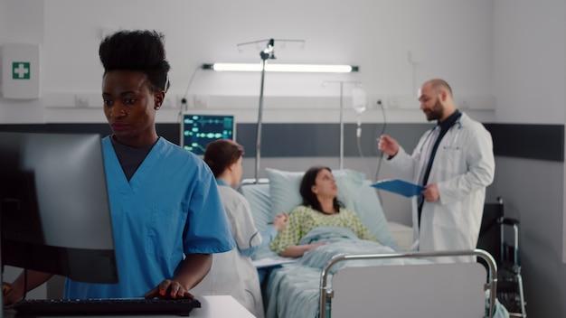 Infirmière noire tapant le symptôme de la maladie pendant que des médecins praticiens spécialistes vérifient une femme malade