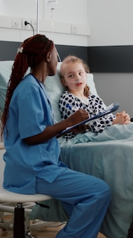 Infirmière pédiatre afro-américaine discutant des symptômes de la maladie avec un petit enfant malade