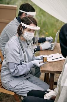 Infirmière portant un masque d'écran en plastique et des gants assis à table à l'extérieur et fournissant des médicaments à...