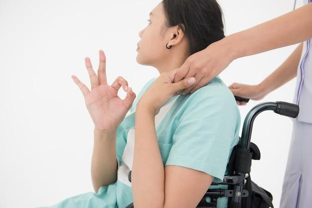 Infirmière poussant un fauteuil roulant du patient
