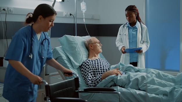 Infirmière préparant le fauteuil roulant pour le patient malade dans la salle d'hôpital