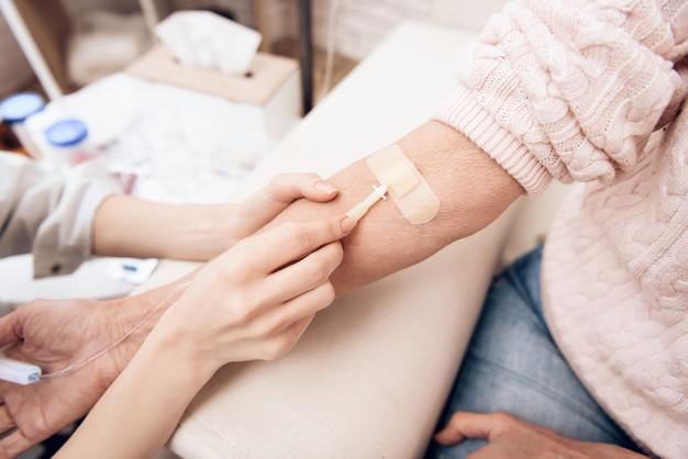 Infirmière prépare un compte-gouttes pour une vieille femme malade