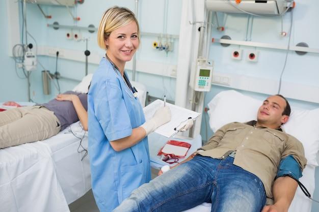 Infirmière regardant la caméra à côté des patients transfusés