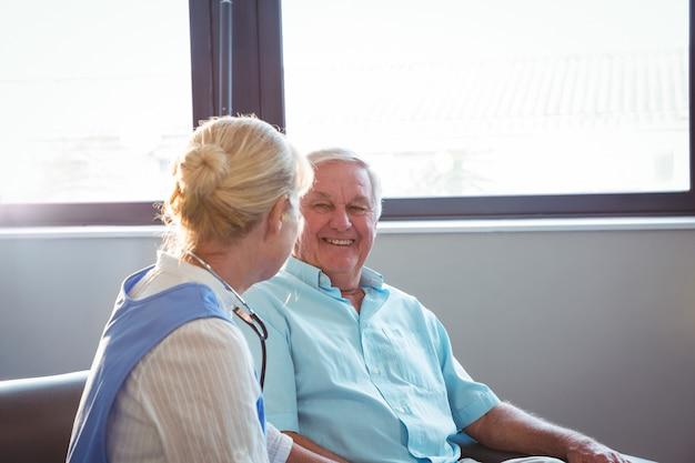 Infirmière et senior homme assis sur un canapé