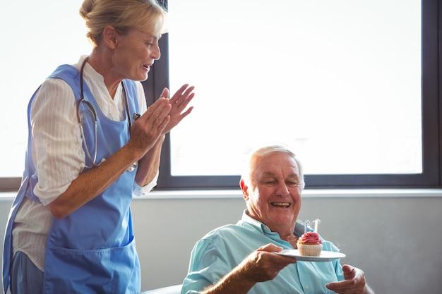 Infirmière et senior homme fête son anniversaire avec muffin