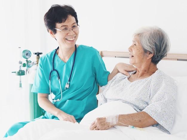 Infirmière senior prendre soin de femme âgée sur le lit dans la chambre d'hôpital.