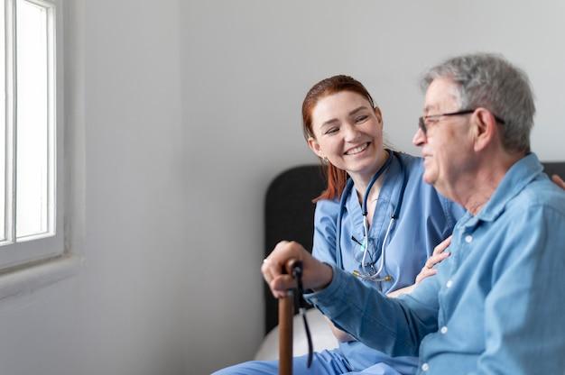 Infirmière smiley coup moyen vérifiant l'homme