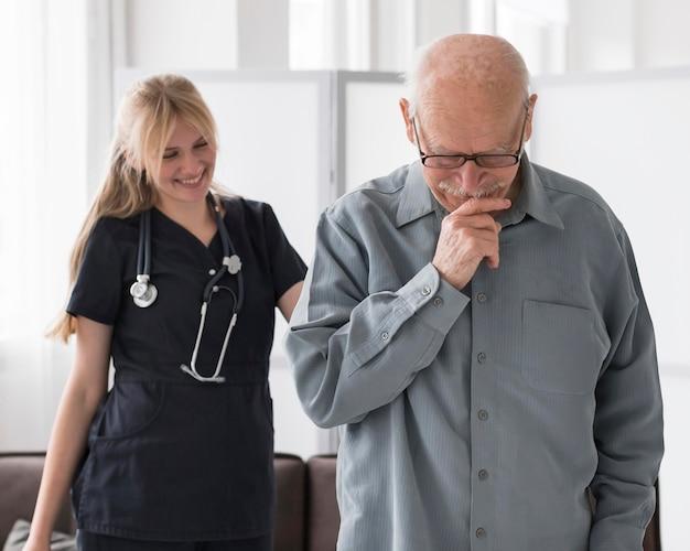 Infirmière smiley avec vieil homme dans une maison de retraite