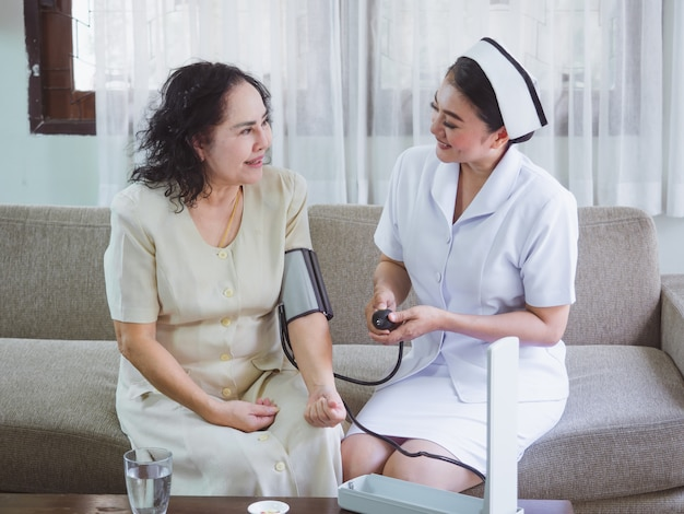 L'infirmière soigne avec bonheur les personnes âgées, les femmes mesurent la pression exercée sur les personnes âgées