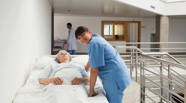 Infirmière souriant à côté d'une vieille dame