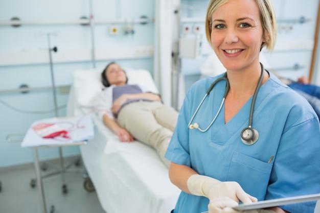 Infirmière souriante debout à côté de patients transfusés