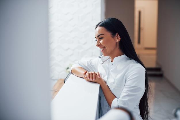 Une infirmière souriante et positive se tient à la réception de la clinique et s'appuie sur la table.