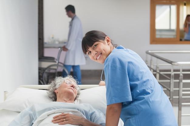 Infirmière souriante s'appuyant sur le lit d'un patient