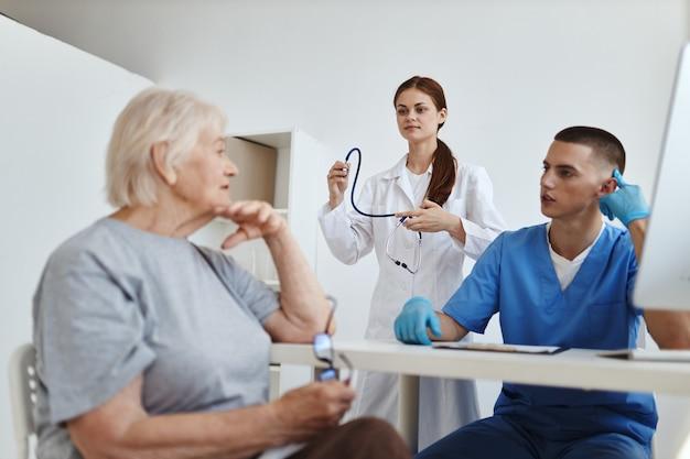 Une infirmière avec un stéthoscope dans les mains à côté d'un médecin diagnostiquant un patient