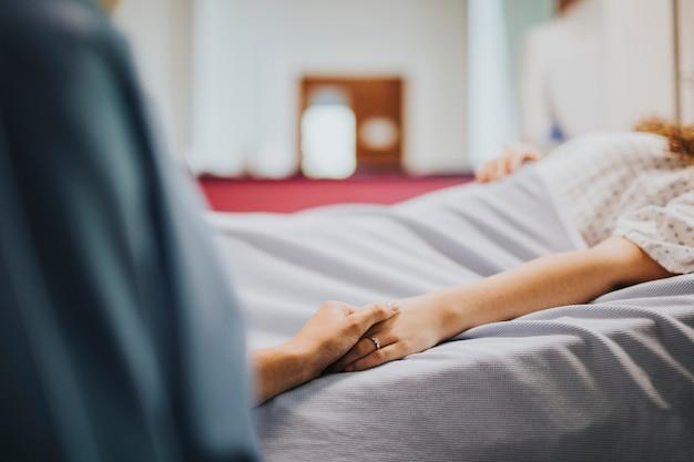 Infirmière tenant la main de ses patients