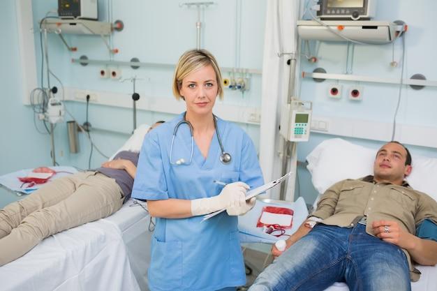 Infirmière tenant un presse-papiers à côté des patients transfusés