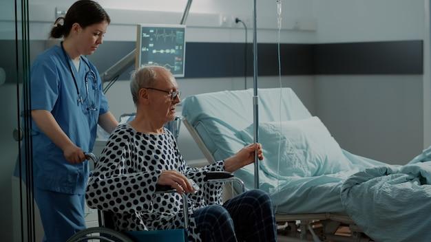 Infirmière transportant un vieux patient en fauteuil roulant jusqu'à la salle d'opération