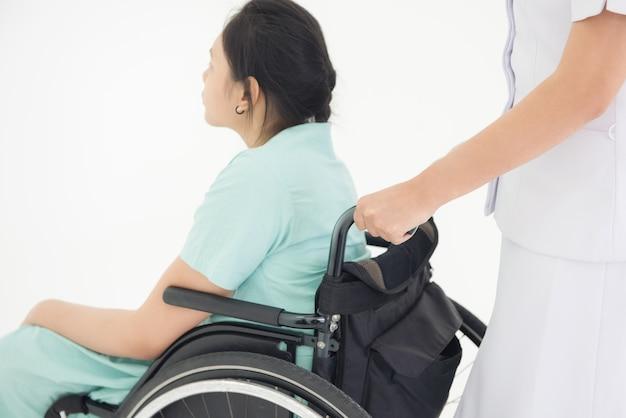 Infirmière en uniforme blanc poussant un fauteuil roulant en costume vert