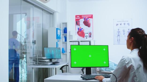 Infirmière en uniforme bleu quittant le cabinet de l'hôpital et médecin utilisant un ordinateur avec écran remplaçable. ordinateur avec écran remplaçable utilisé par un spécialiste de la médecine à l'hôpital et en uniforme.