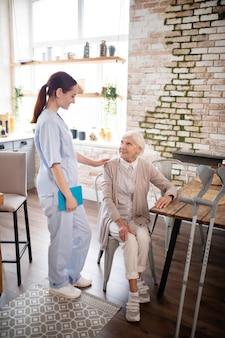 Infirmière utile portant l'uniforme parler au patient