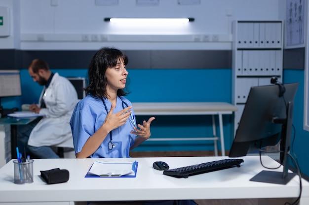 Infirmière utilisant l'appel vidéo avec webcam sur ordinateur