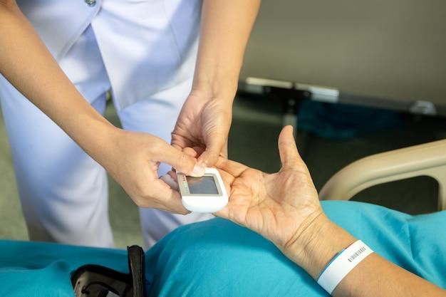 Infirmière vérifiant la glycémie à l'aide d'un glucomètre à l'hôpital.