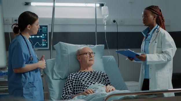Infirmière vérifiant l'oxymètre sur le patient malade dans la salle d'hôpital