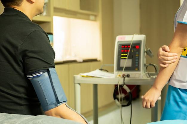 Infirmière vérifiant la pression artérielle sur l'écran du moniteur pour la santé du patient à l'hôpital.