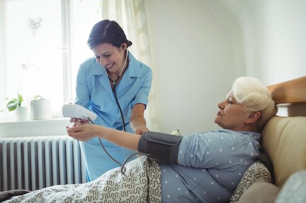 Infirmière, vérification, tension artérielle, de, femme aînée