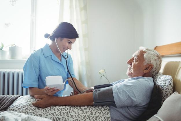 Infirmière, vérification, tension artérielle, de, homme aîné