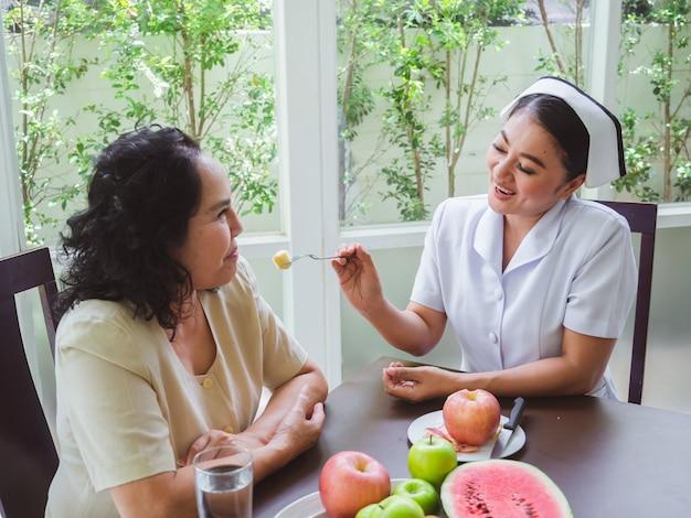 Les infirmières donnent des pommes aux personnes âgées