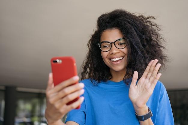 Influenceur afro-américain enregistrant une vidéo parlant avec des abonnés femme heureuse ayant un appel vidéo