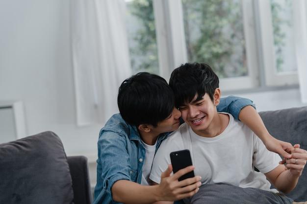 Influenceur asiatique couple gay vlog à la maison. les hommes lgbtq asiatiques heureux se détendent en utilisant la technologie en enregistrant des vidéos sur le téléphone mobile en enregistrant des vidéos sur les réseaux sociaux tout en restant allongés dans le salon.