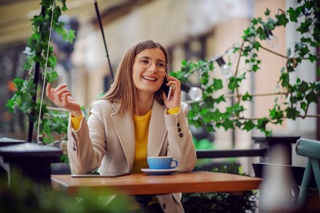 Influenceur assis sur la terrasse de la cafétéria, prenant une pause-café et discutant au téléphone avec un ami.
