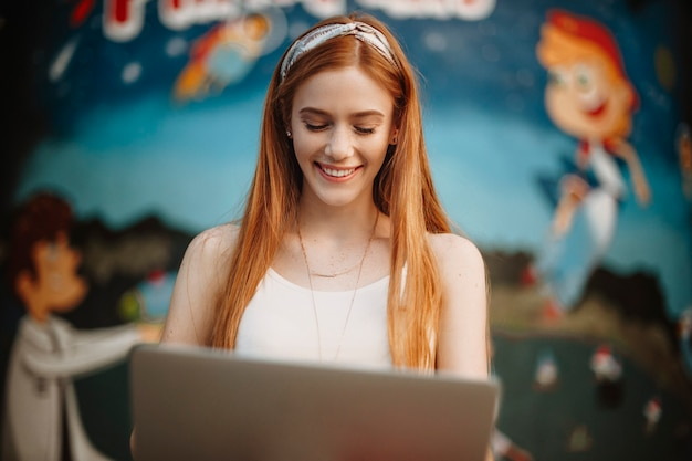 Influenceur de jeune femme charmante regardant son écran d'ordinateur portable souriant sur un fond bleu. femme aux cheveux rouges avec des taches de rousseur riant en plein air.
