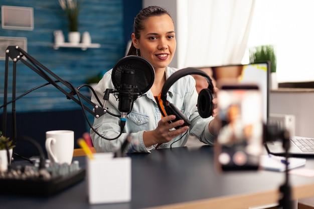 Influenceur présentant des écouteurs à offrir à la caméra tout en créant un blog vidéo dans un home studio. influenceur créateur de contenu créatif enregistrant un cadeau de podcast web en ligne pour le public