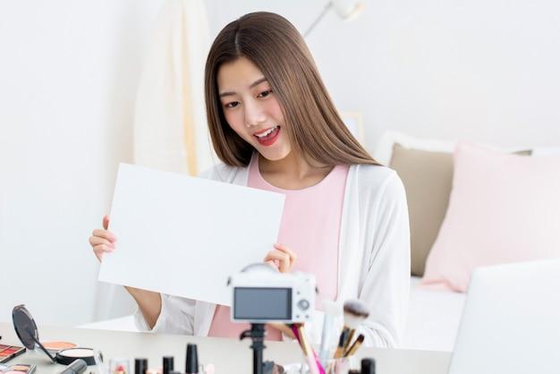 L'influenceuse de beauté femme communique avec le public en montrant du papier blanc avec un espace pour vos textes