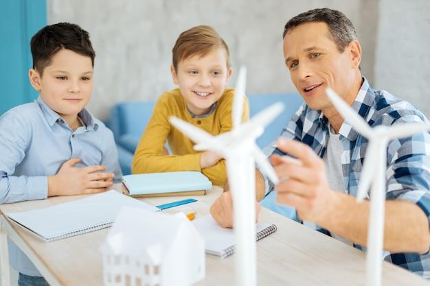 Une information intéressante. agréable père optimiste montrant les modèles d'éoliennes debout sur sa table et discutant de leur construction avec ses fils curieux