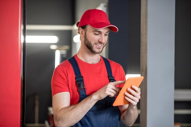 Informations. homme souriant intéressé en bonnet rouge et salopette bleue à la recherche de tablette tactile doigt à écran dans le garage