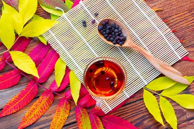 Infusion d'aubépine dans un bol en verre, une cuillère en bois avec fruits secs et natte de bambou
