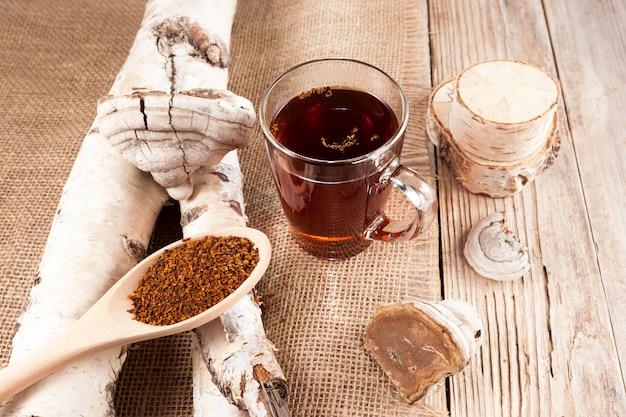 Infusion de champignons chaga dans une tasse en verre, style rustique.