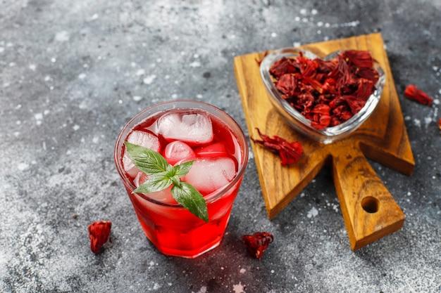 Infusion froide de thé d'hibiscus avec de la glace et des feuilles de basilic.