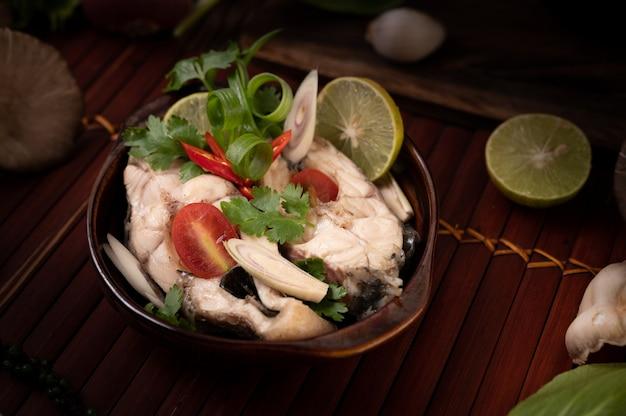 Infusion de poisson bouilli aux tomates, champignons, coriandre, ciboule et citronnelle dans un bol
