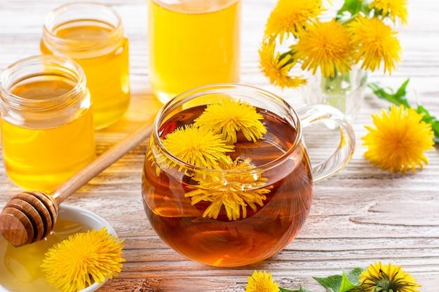 Infusion de tisane de feuilles de pissenlit fraîches, avec des fleurs jaunes et du miel sur une table en bois blanc